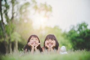 Little girls lying comfortably on the grass and smiling