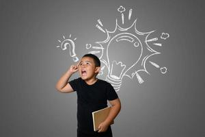 Confused young boy on neutral chalkboard background photo