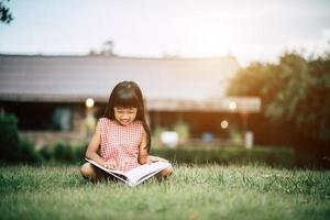 Little girl reading a book in her house garden outside