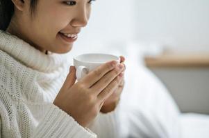 mujer joven, tenencia, un, taza de café, en cama foto
