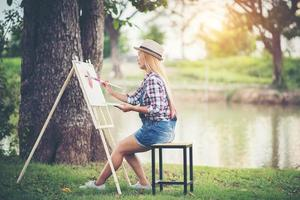 Beautiful girl drawing a picture in the park