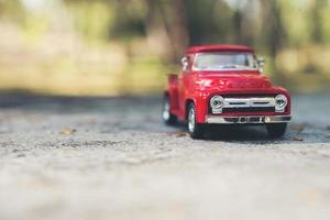 Mini red toy truck parked in the road photo