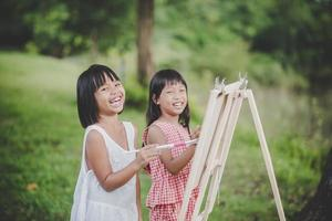Two little girl painters drawing art in the park