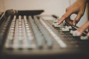 Hands of sound engineer adjusting audio mixing console