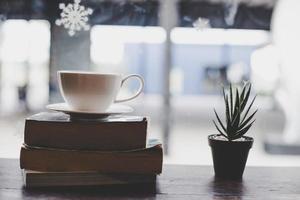 Tono de color vintage taza de café con libro en una cafetería. foto