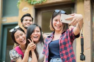 Group of friends taking a selfie in an urban street having fun together