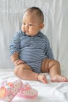 A baby learning to sit on a white bed photo