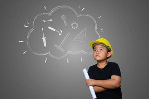 A boy wearing a yellow engineer hat and a house plan on blackboard