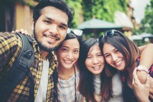 Group of friends taking a selfie in an urban street having fun together photo