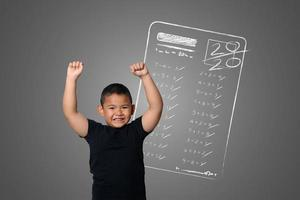 Young boy shows full marks in school tests on the blackboard