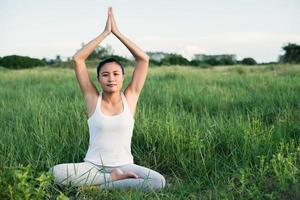 Young yoga woman sits in meditation in the meadows photo