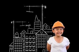 Young boy wearing an engineer hat and a house plan on a blackboard