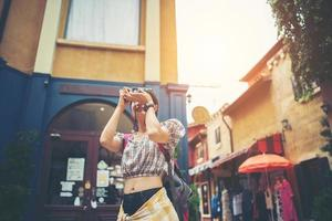 Young hipster woman taking photos in an urban area
