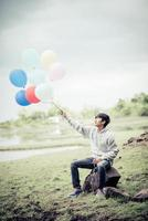 Young man holding colorful balloons in nature