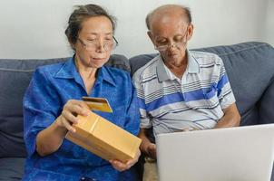 Two elderly people shopping online