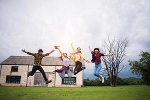 Happy group of teen students jumping in a park together