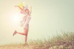 joven y bella mujer sosteniendo globos al aire libre foto