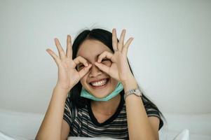 niña con máscara sanitaria, camisa a rayas y símbolo de la mano bien foto