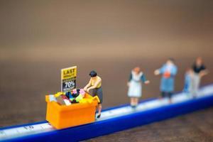 Gente en miniatura comprando en un contenedor de descuento