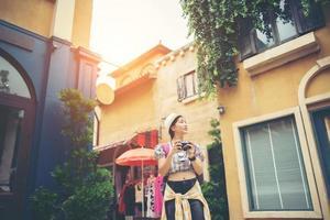 Mujer joven inconformista disfrutando de tomar una foto en el entorno urbano