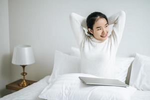 mujer joven, estirar cama, con, computador portatil