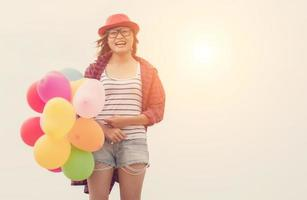 Young beautiful woman holding balloons in the fresh air photo
