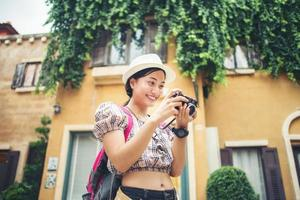 Young hipster woman enjoying taking a photo in urban setting