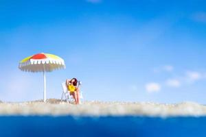 Persona de figurillas en miniatura tomando el sol en la playa