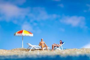 Figurilla en miniatura de personas tomando el sol en la playa