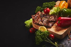 bistec y verduras sobre fondo oscuro