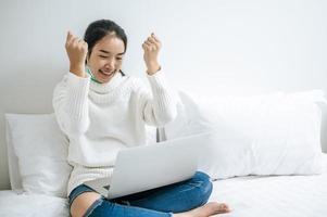 mujer joven, llevando, un, camisa blanca, juego, en, ella, computador portatil foto