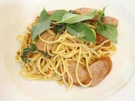 Espaguetis con salchicha ahumada en la placa blanca.