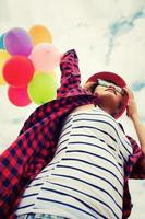 Teenage girl holding colorful balloons in the bright sky photo