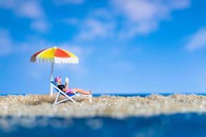 Miniature figurine person sunbathing on the beach photo