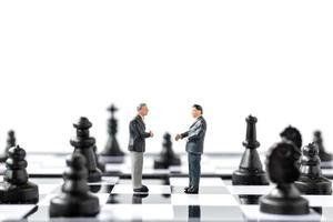 Figuras en miniatura de empresarios de pie sobre un tablero de ajedrez foto