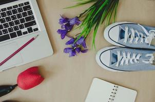 Laptop, shoes, and flowers on brown background