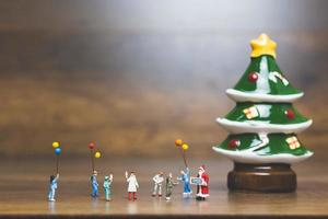 Miniature figurines of people putting up Christmas decorations