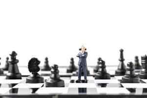 figura en miniatura de empresario y tablero de ajedrez