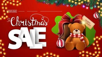 Christmas sale, modern red discount banner with large white volumetric letters, garlands, green blot, Christmas tree branches and present with Teddy bear vector