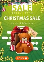 Special offer, Christmas sale, up to 50 off, green vertical banner with Christmas tree branches, garlands, button and present with Teddy bear vector