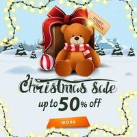 Christmas sale, up to 50 off, square banner with winter landscape, pines, drifts, mountain, city on horizont and big present with Teddy bear vector