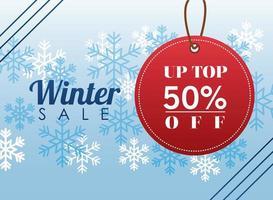 gran cartel de rebajas de invierno con etiqueta circular colgando y copos de nieve vector