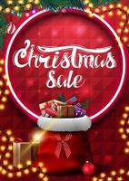 Christmas sale, red vertical banner with garland, christmas tree branches, neon circle, beautiful lettering and Santa Claus bag with presents