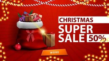 Christmas super sale, up to 50 off, red discount banner with Santa Claus bag with presents near the wall