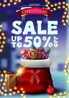Christmas discount banner with garland and Santa Claus bag with presents. Vertical discount banner with blurred winter landscape on the background