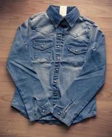 Camisa de mezclilla azul sobre piso de madera