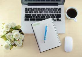 computadora, cuaderno y café en el escritorio foto