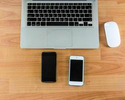 Two smart phones and laptop on desk top