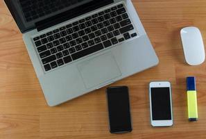 Laptop and smart phones on desk photo
