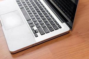 Corner of laptop on wooden desk photo